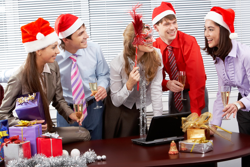 Portrait of happy business people chatting while celebrating Christmas in office